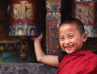 Child at prayer wheel in Bhutan by Mark Tuschman