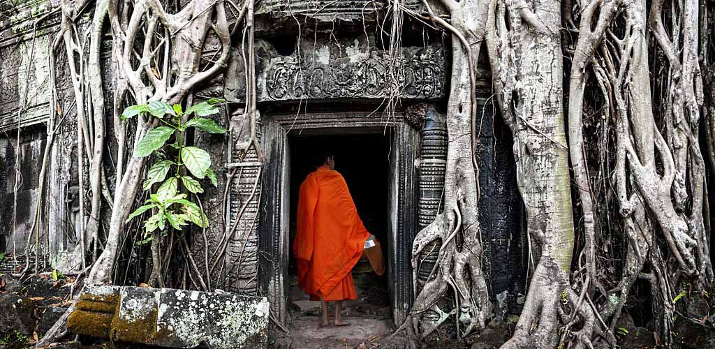 Monk entering Ta Phrom temple in Angkor