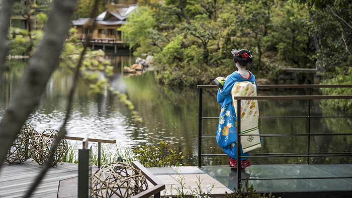 Geisha looking over a pond at the Four Seasons in Kyoto, Japan