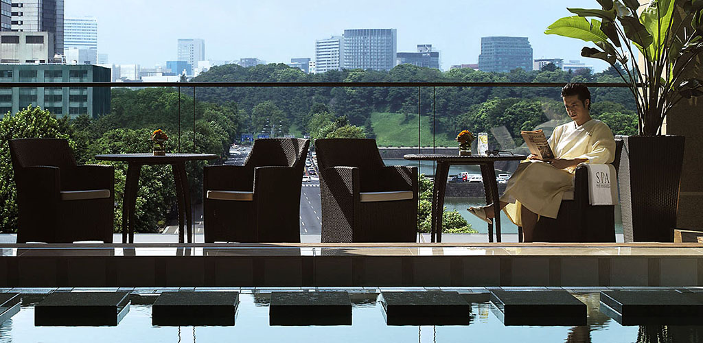 Man reading on terrace at Peninsula luxury hotel, Tokyo, Japan