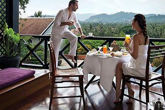 Couple having breakfast on verandah at luxury hotel La Residence Phuo Vao
