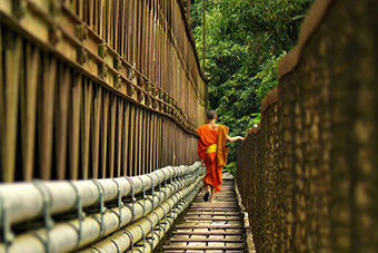 Monk crossing bamboo bridge in Luang Prabang, Laos
