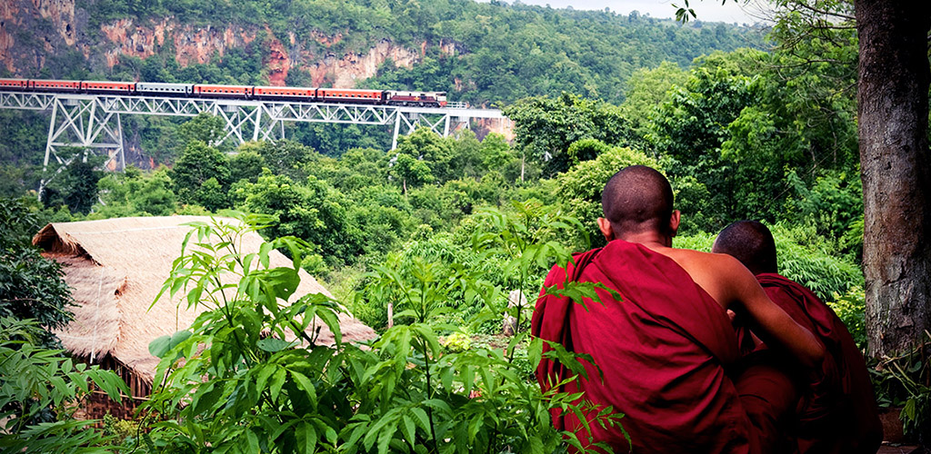 Monks look at train on Goteik Aqueduct in Myanmar