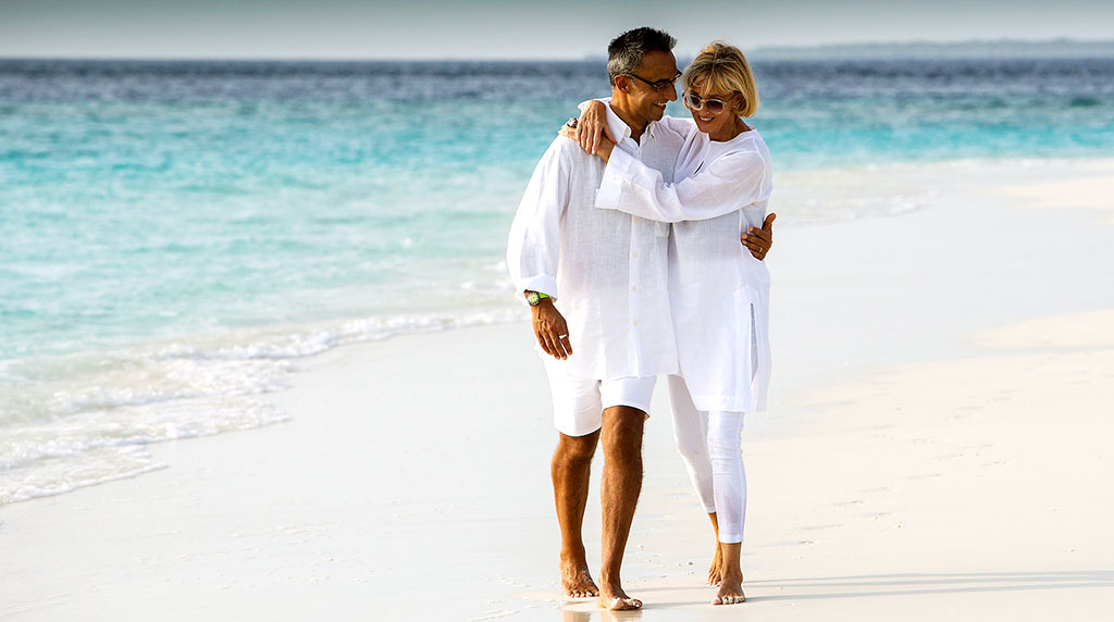 Couple walking along the beach at the Sonevi Kiri luxury resort on Koh Kood, Thailand