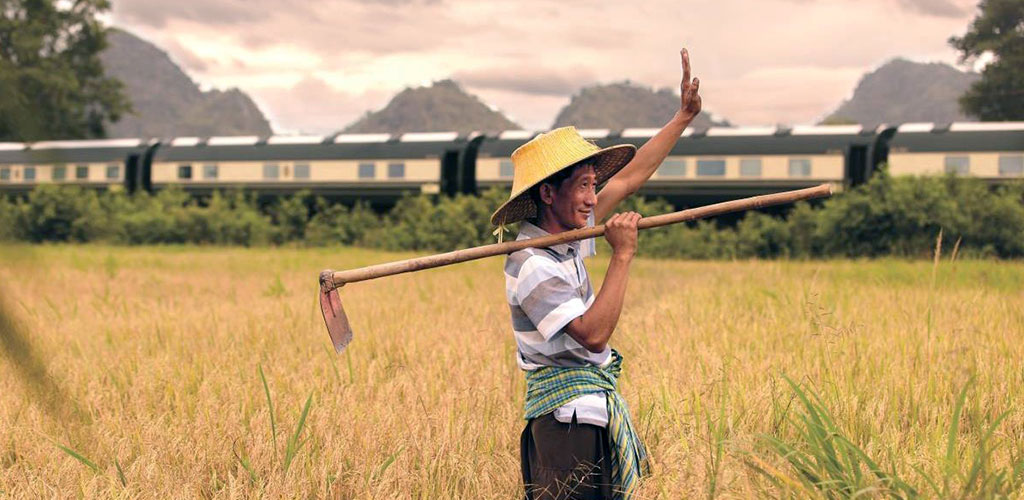 Eastern Orient Express luxury train passing by farmer in Thailand