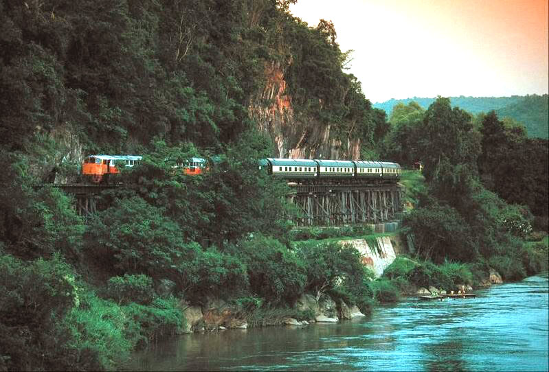 Eastern Orient Express luxury train passing by river in Thailand