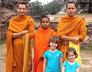 Posing with monks during family tour of Thailand