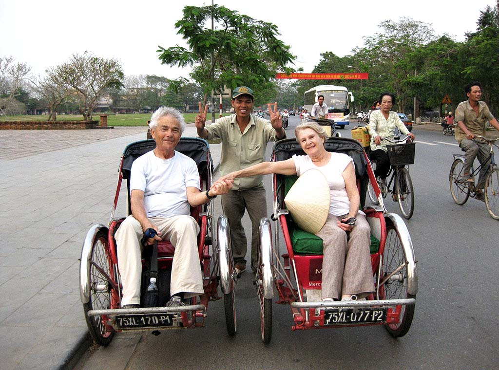 Couple enjoying cyclo tour of Hanoi