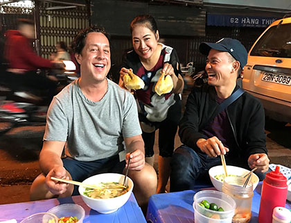 Eating pho on the street in Hanoi during street food tour of the capital city