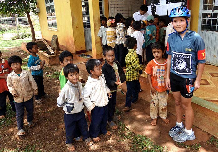 Boy with schoolchildren on family cycling tour in Vietnam