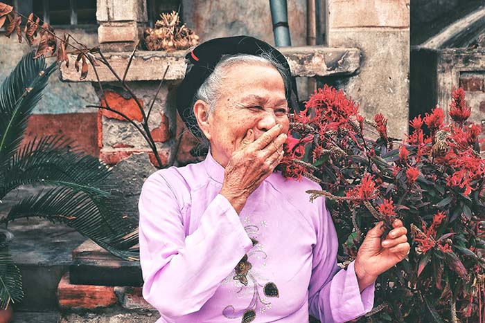 Old woman in Hanoi with flowers in Hanoi, Vietnam